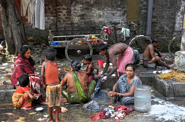 KOLKATA, INDIA - 27 OCTOBER, 2009: An unidentified group of Indian people wash themselves on a street of Kolkata on October 27, 2009.