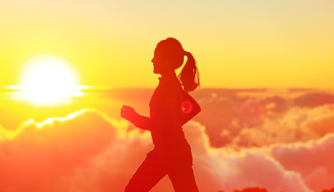 Runner woman running in sunshine sunset. Fitness athlete training trail running marathon in mountains above the clouds in beautiful mountain landscape. Female in jogging in silhouette.