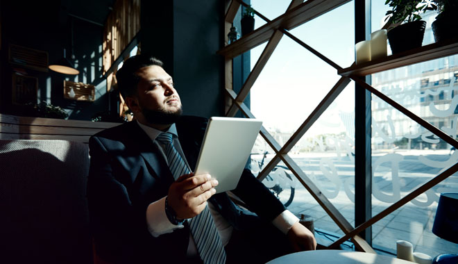 Portrait of mature handsome businessman using digital tablet 4g app working in a coffee shop, adult man thinking and looking out the window