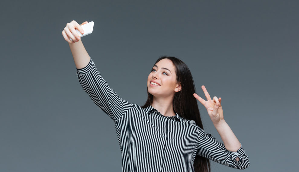 Smiling businesswoman making selfie photo on smartphone over gray background